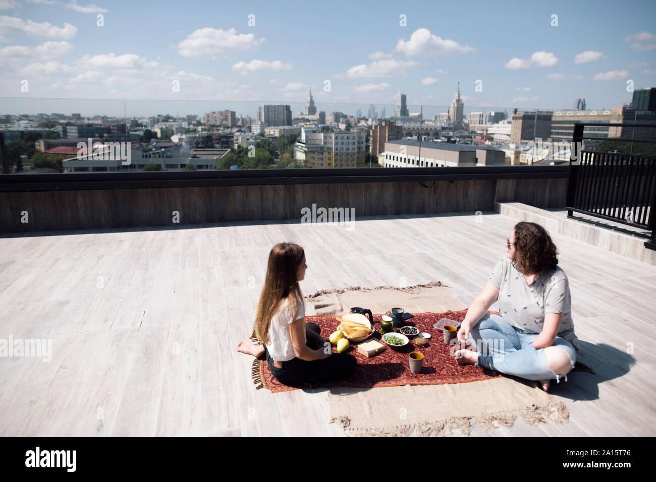 Mujer con infra-codo amputación y niñas tuvieran una comida saludable en el techo Foto de stock