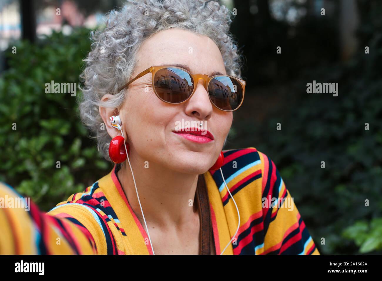 Retrato de mujer madura traspasado con gafas de sol y auriculares Foto de stock