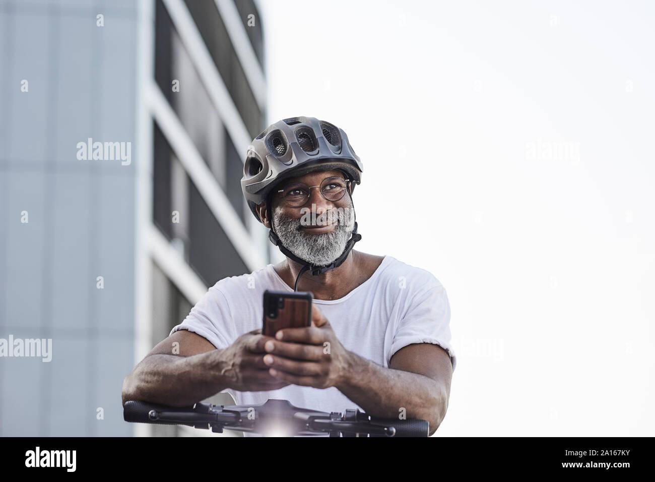 Retrato del hombre maduro feliz llevar casco de ciclista inclinado sobre el manillar de Scooter eléctrico Foto de stock
