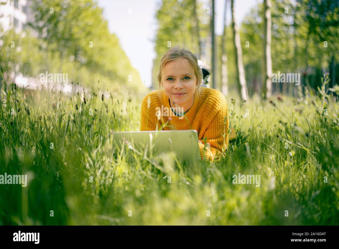 Retrato de mujer sonriente tumbado en una pradera utilización portátil Foto de stock