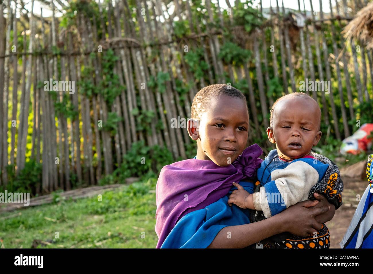 Niños masai en la vestimenta tradicional son responsables de sus hermanos menores en la aldea. Foto de stock