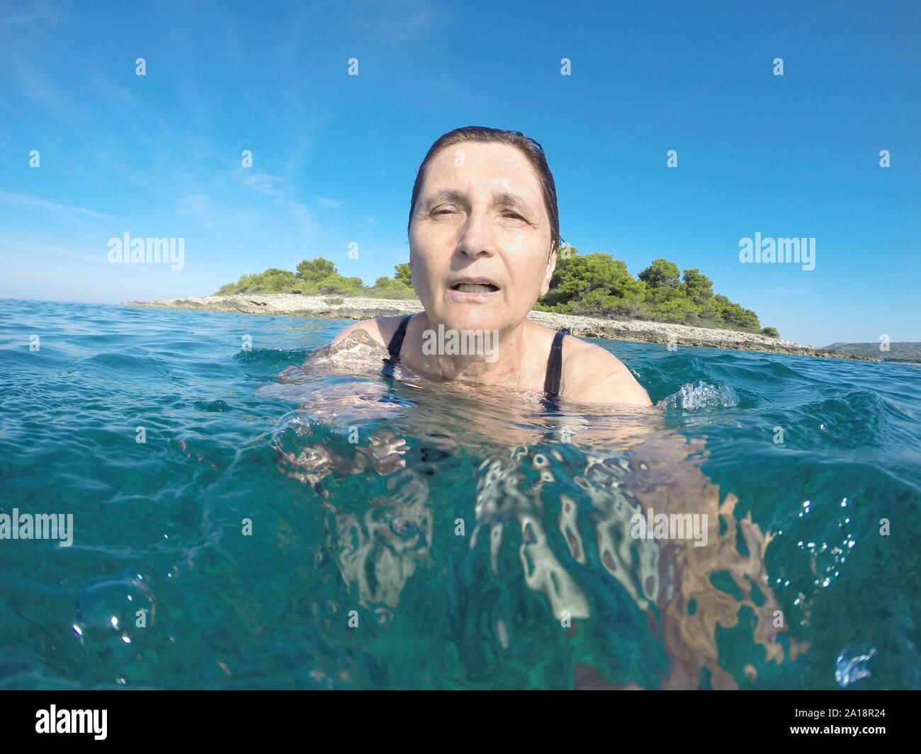 Mujer madura, nadando en el azul claro del mar Adriático Foto de stock