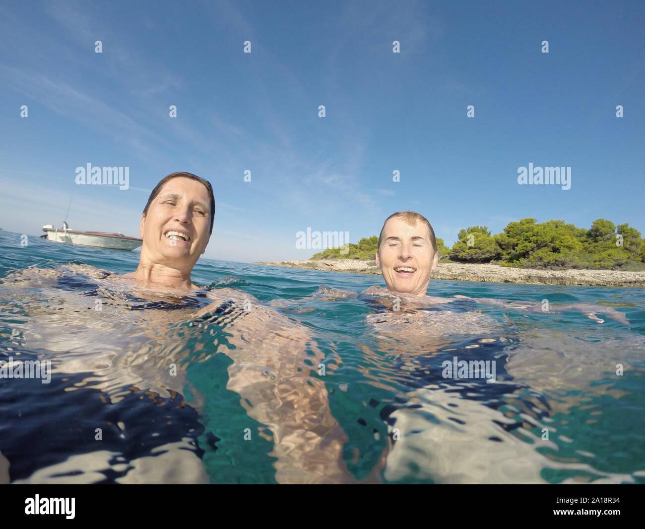 Dos mujeres nadando en el azul claro del mar Adriático Foto de stock