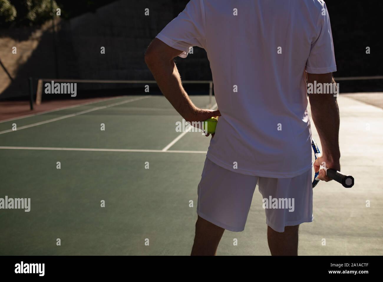 Hombre jugando al tenis en un día soleado Foto de stock