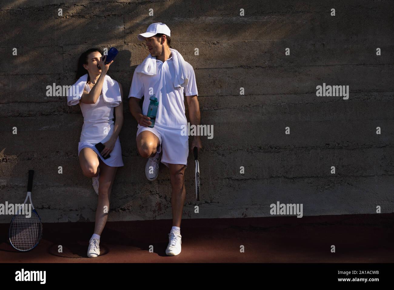 Mujer y hombre, tomando un descanso durante un partido de tenis Foto de stock