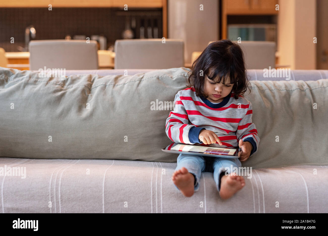 Niña sentada en su sofá con una tableta digital Foto de stock