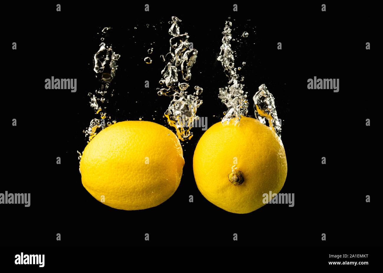 Fresh water splash en limones amarillos sobre fondo negro con un montón de burbujas de aire. Foto de stock