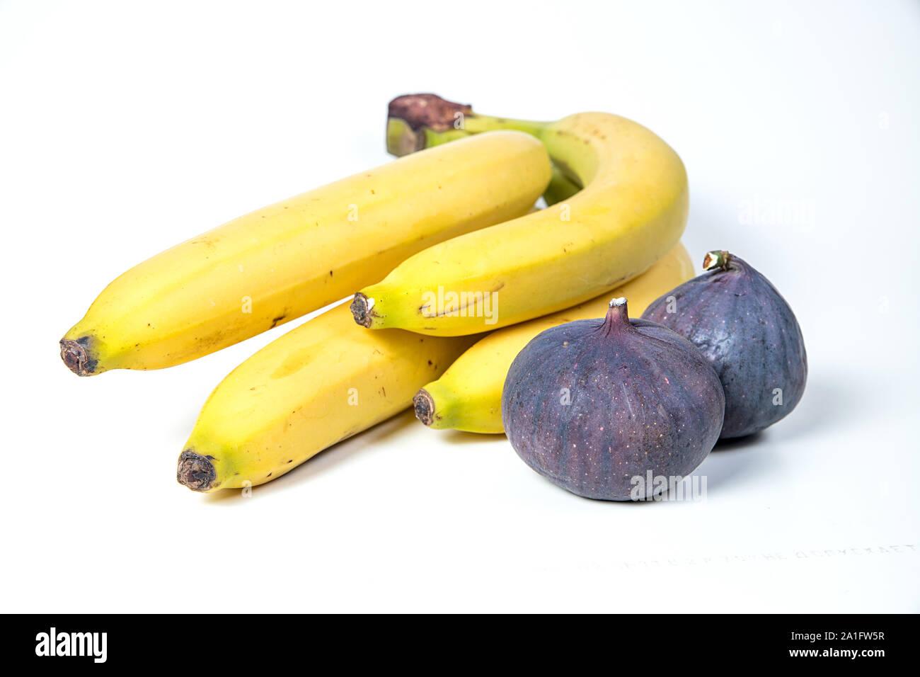 Los higos y plátanos, hermosos frutos, plátanos, higos, púrpura cerca, concepto de vitaminas, la alimentación vegetariana, comer sano, Foto de stock