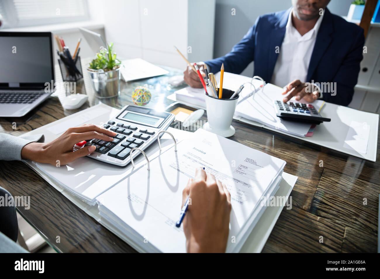 Dos compañeros de trabajo Cálculo de impuestos en la oficina Foto de stock