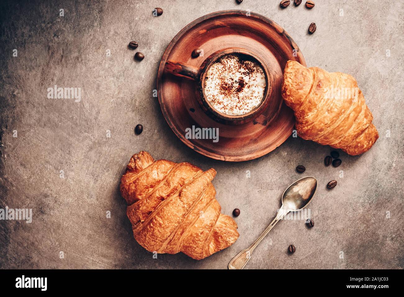 Los cruasanes y café caliente en una taza vintage oscuro sobre un fondo de textura rústica en tonos marrones. Vista desde arriba, laicos plana Foto de stock