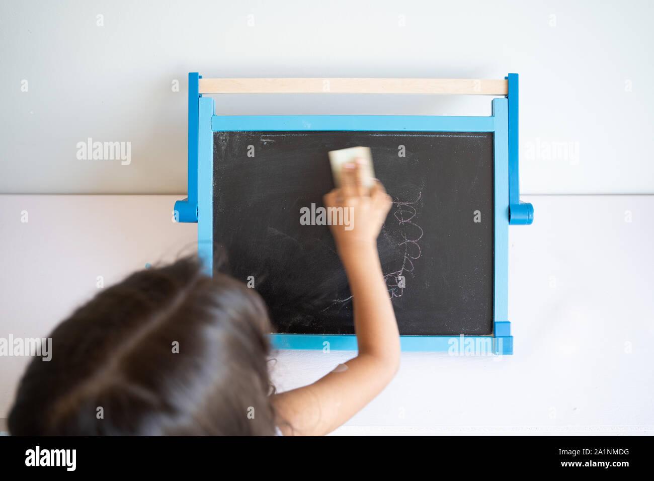La pequeña niña con cabello marrón largo borrar pequeña pizarra blanca con alrededores visto desde atrás Foto de stock