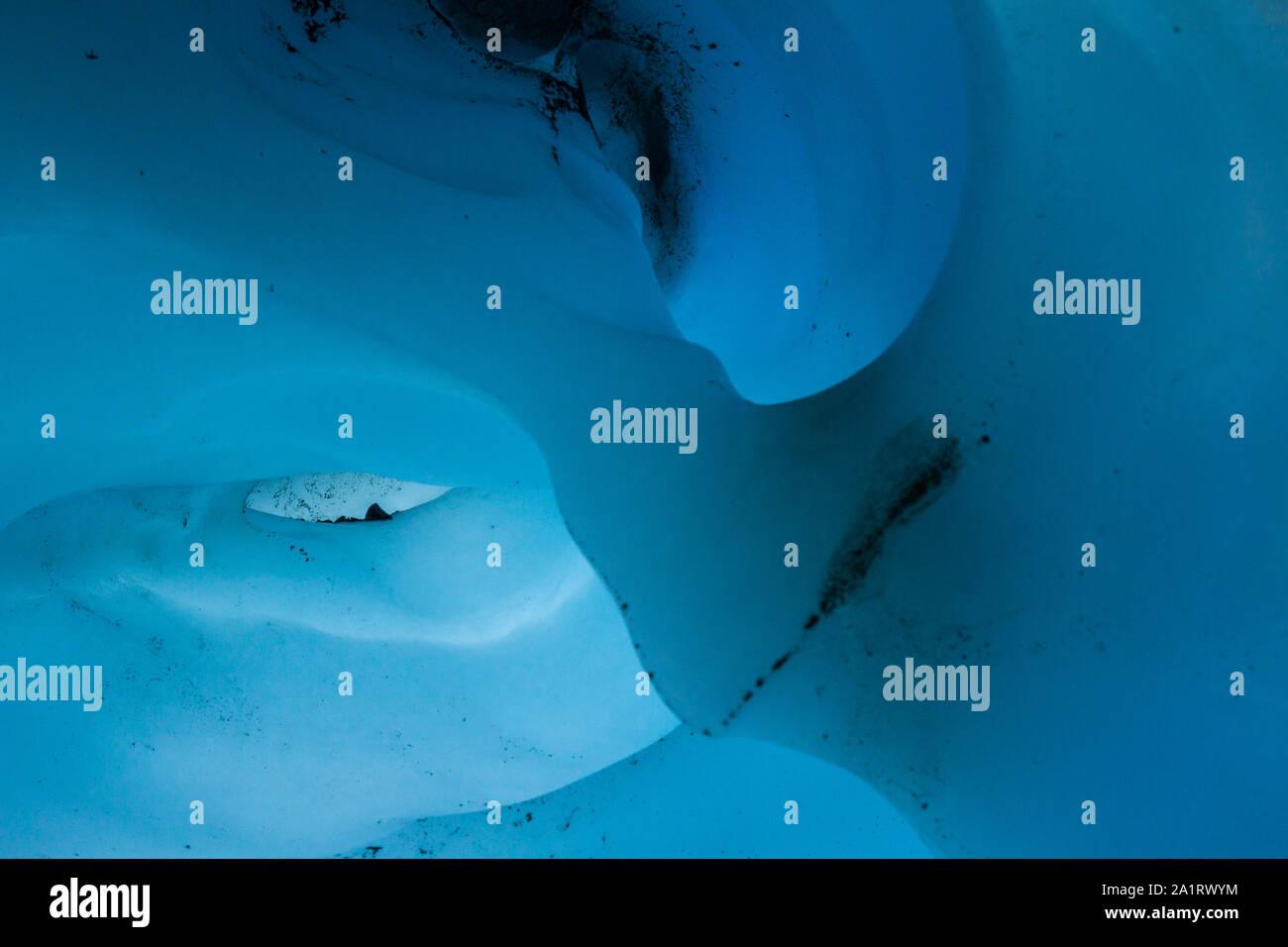 Cortar un arco de hielo glaciar tiene el aspecto de una nariz, mientras dos huecos parecen crear sockets en ojo de hielo de formas extrañas en el interior de una cueva de hielo en Alaska. Foto de stock