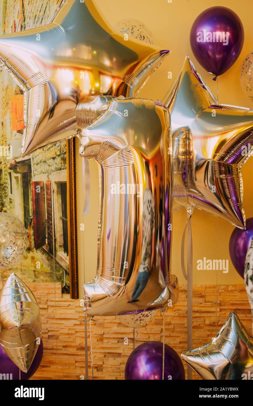 Decoración para 1 años, cumpleaños, aniversario. Globo número uno. El dígito es una unidad de color oro. Los Globos de oro y púrpura. Celebración de la h Foto de stock