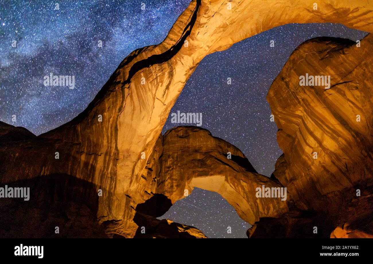 Mirando hacia icónico Arco Doble encendido contra un lleno de estrellas de la Vía Láctea en el Parque Nacional de Arches en Moab, Utah. Foto de stock