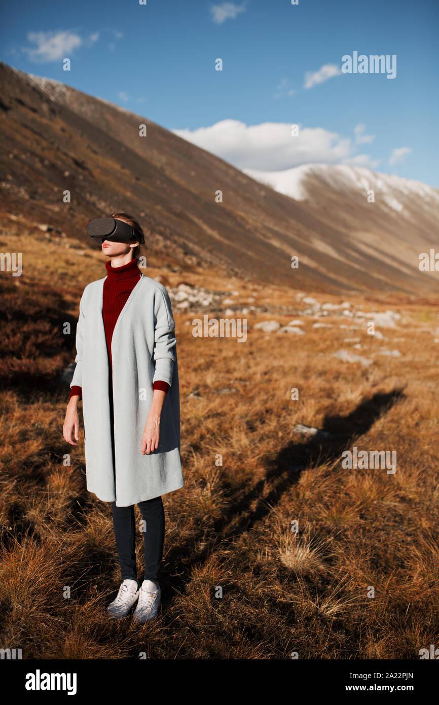 Mujer en la realidad virtual. Paisaje de montaña en el fondo. Foto de stock