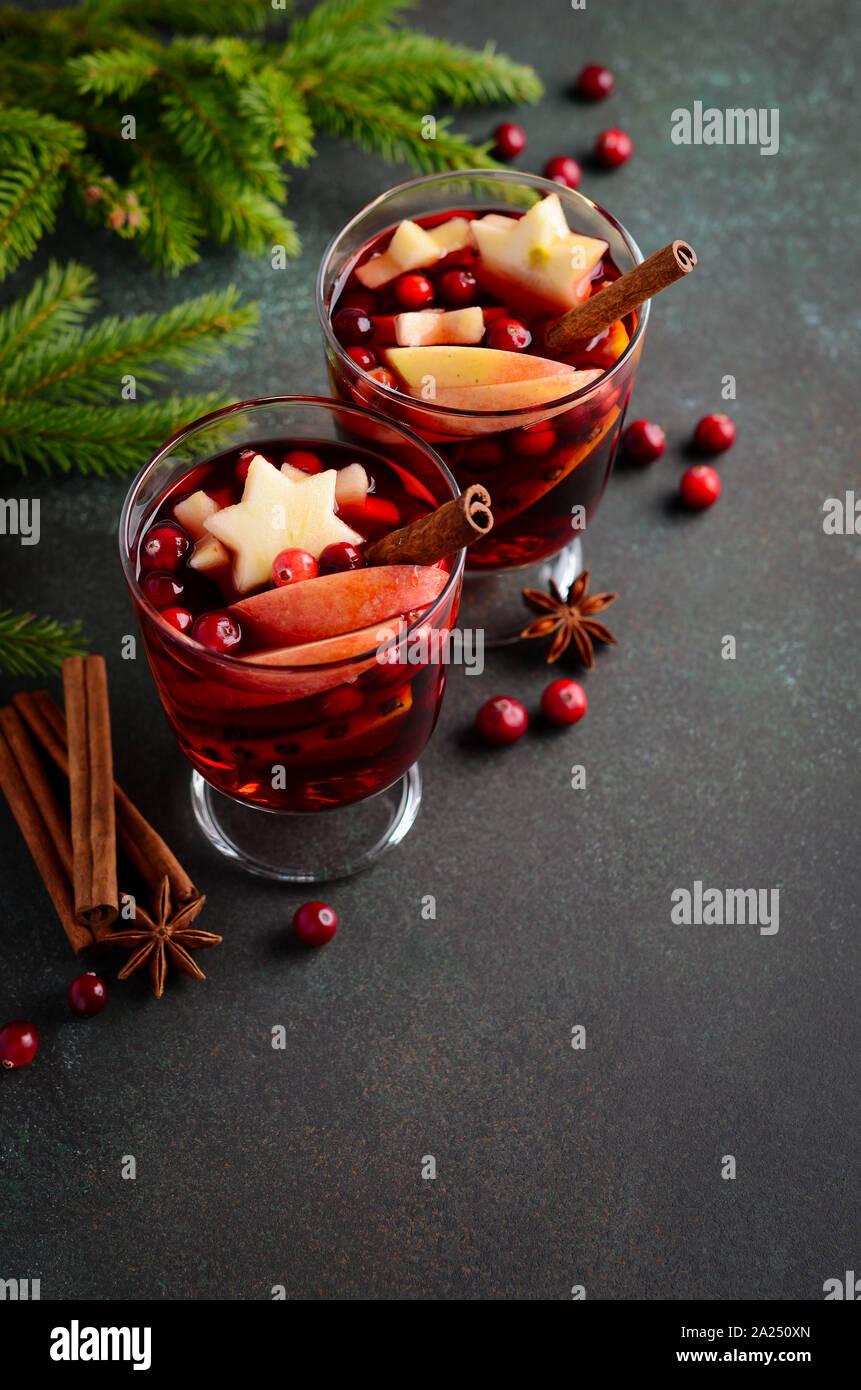 Vino especiado de navidad con manzana, naranja y arándanos. Concepto de vacaciones decorado con ramas de abeto, arándanos rojos y especias. Foto de stock