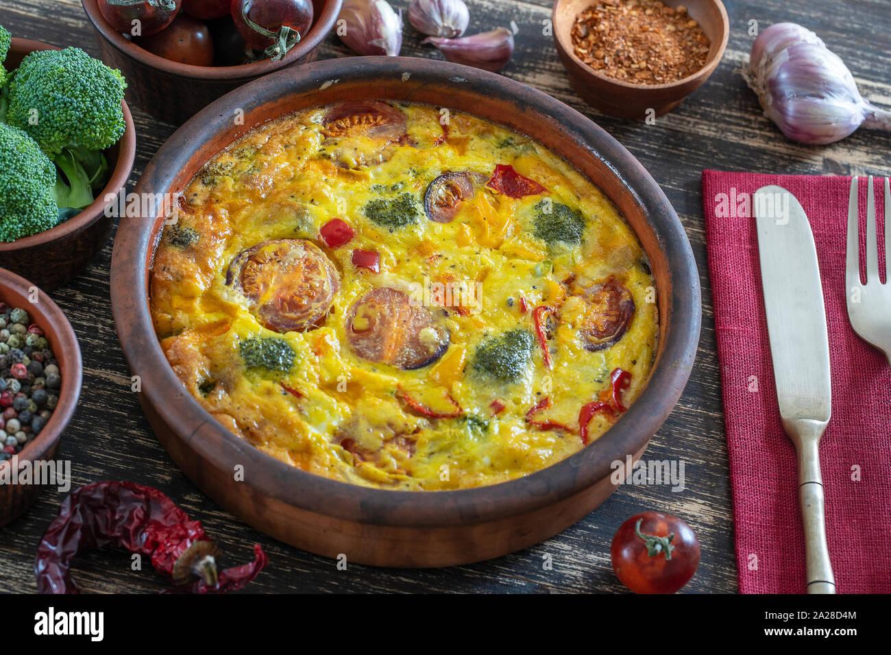 Cuenco de cerámica con verdura frittata, sencilla comida vegetariana. Frittata con huevo, tomate, pimiento, cebolla, brócoli y queso en la mesa de madera, de cerca. Foto de stock