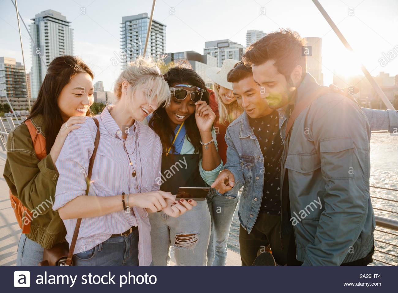 Feliz adulto joven amigos usando la tableta digital en los soleados, puente urbano Foto de stock