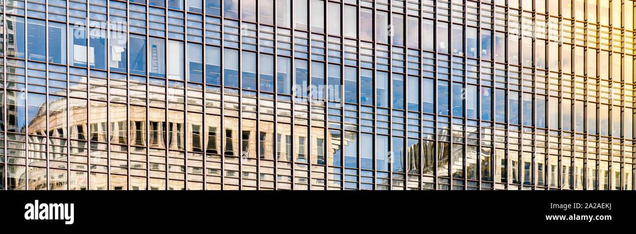 Panorámica de un edificio moderno de vidrio al atardecer con las nubes reflejándose en las ventanas de vidrio Foto de stock