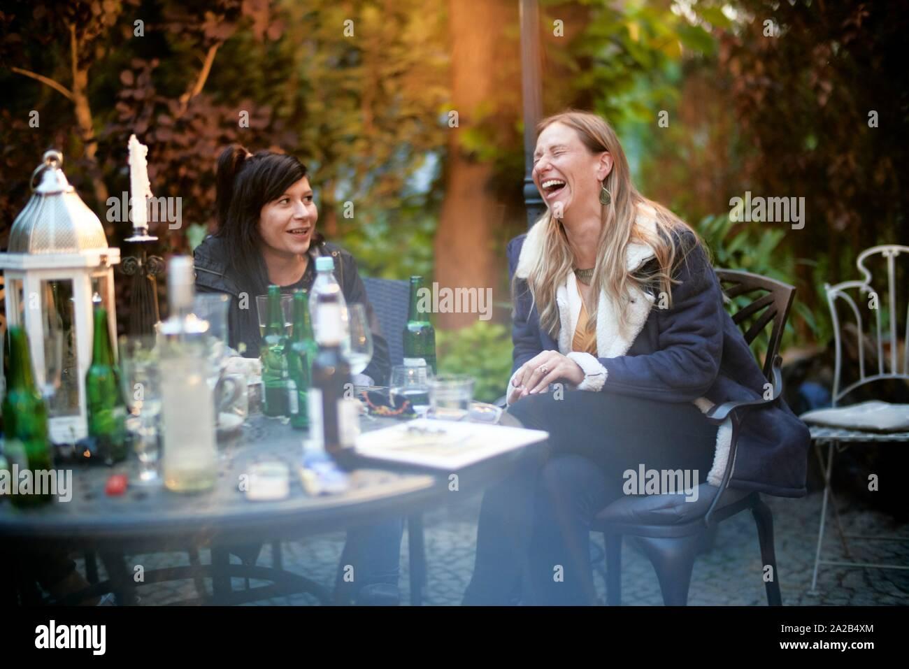 Mujer de mediana edad feliz riéndose de fiesta en el jardín con un amigo Foto de stock