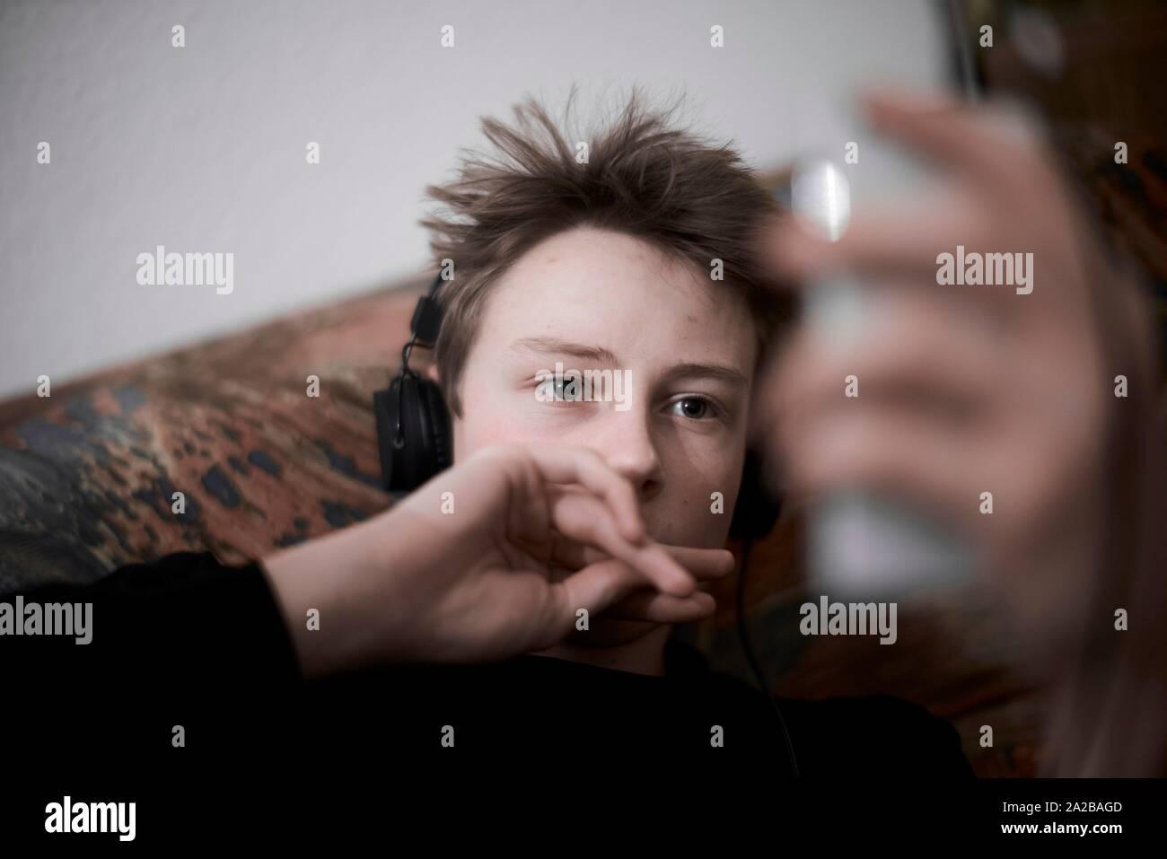 Adolescente (17 años) con entretenimiento smartphone Foto de stock