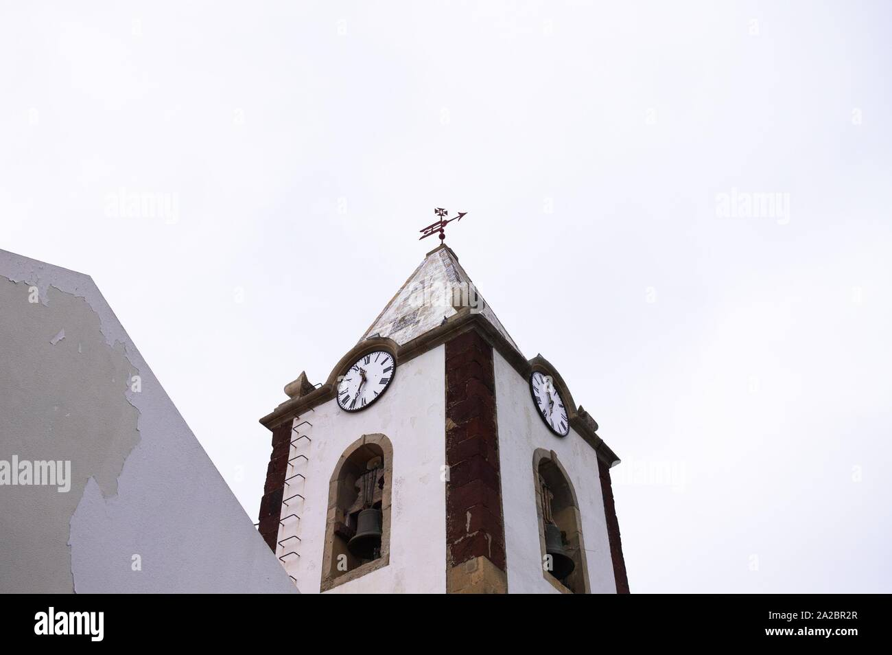 Reloj y campanario de un edificio religioso con un crucifijo en la parte superior (Madeira, Portugal) Foto de stock