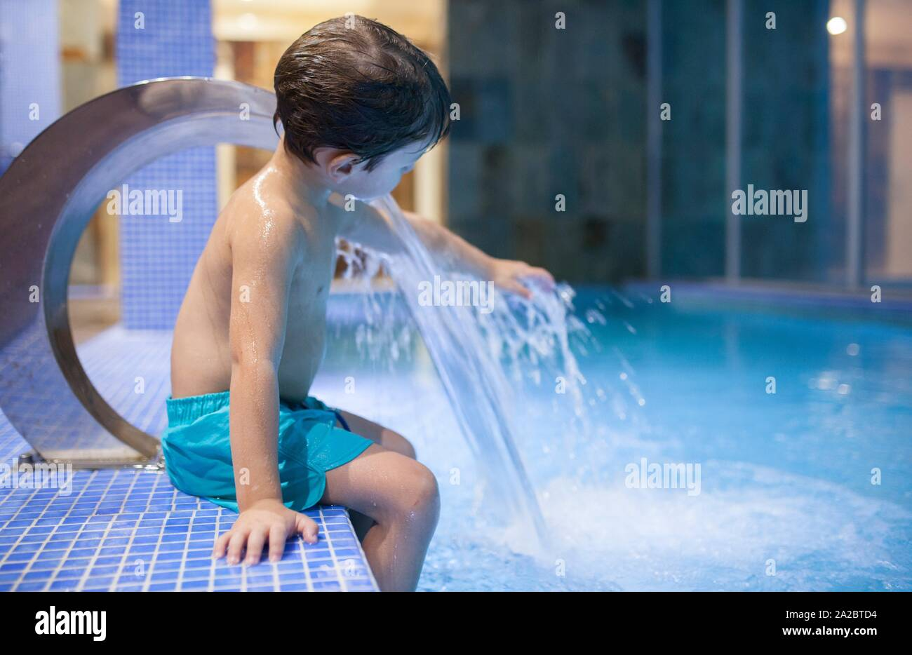 Niño de 4 años jugando en la piscina cubierta con chorros de hidromasaje. El enfoque selectivo. Foto de stock