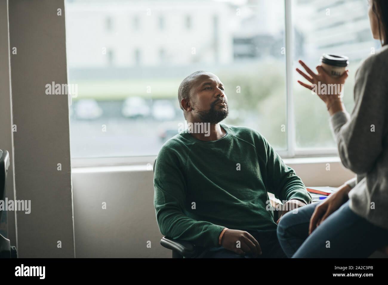 Diseñador americano africano hablando con un colega en el trabajo Foto de stock