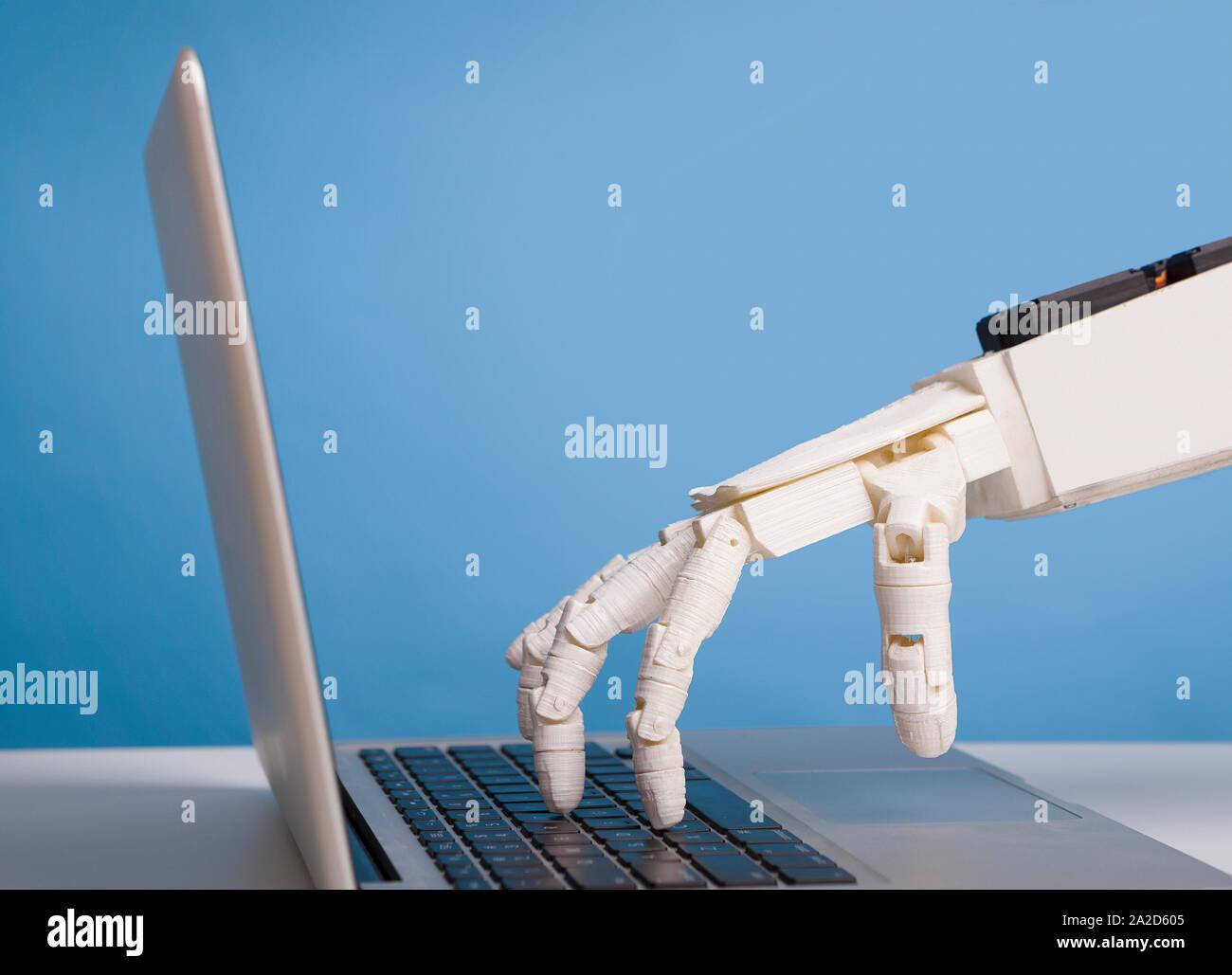 Mano robótica escribiendo en el teclado portátil, espacio libre Foto de stock