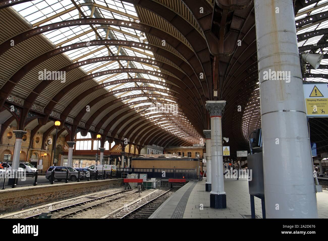 York estación ferroviaria de techo de hierro forjado con arcos y columnas de soporte de hierro fundido a la vuelta de la curva en las plataformas de la estación de York, Yorkshire, Inglaterra Foto de stock