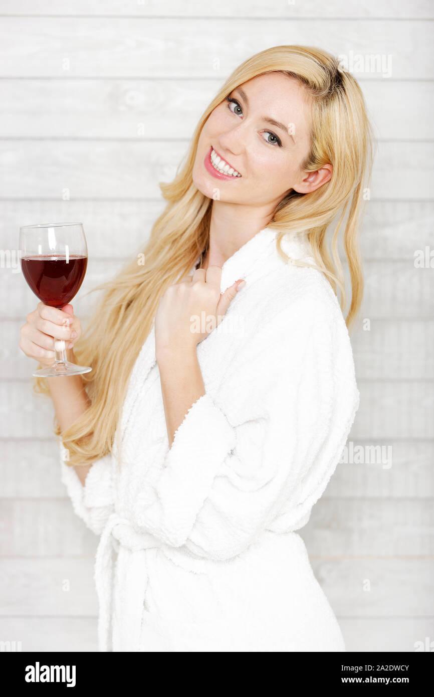 Hermosa joven con una túnica blanca disfrutando de una copa de vino tinto Foto de stock