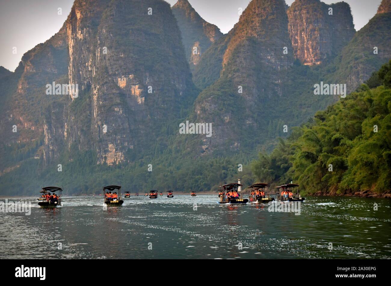 Parque del río Li lanchas turísticas debajo de altos picos montañosos, Guangxi, China Foto de stock