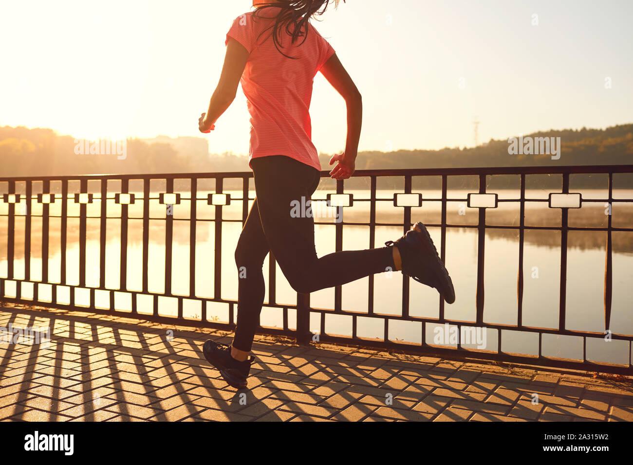 Los corredores piernas corren a lo largo de la carretera por el lago en el parque Foto de stock