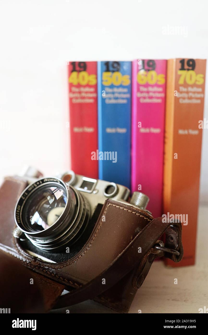 GARCHING, Alemania - 28 de septiembre de 2019 Vintage cámara Leica y libros con una colección de imágenes analógicas significative de los 40s,50s,60s,70s años, por lo que Foto de stock