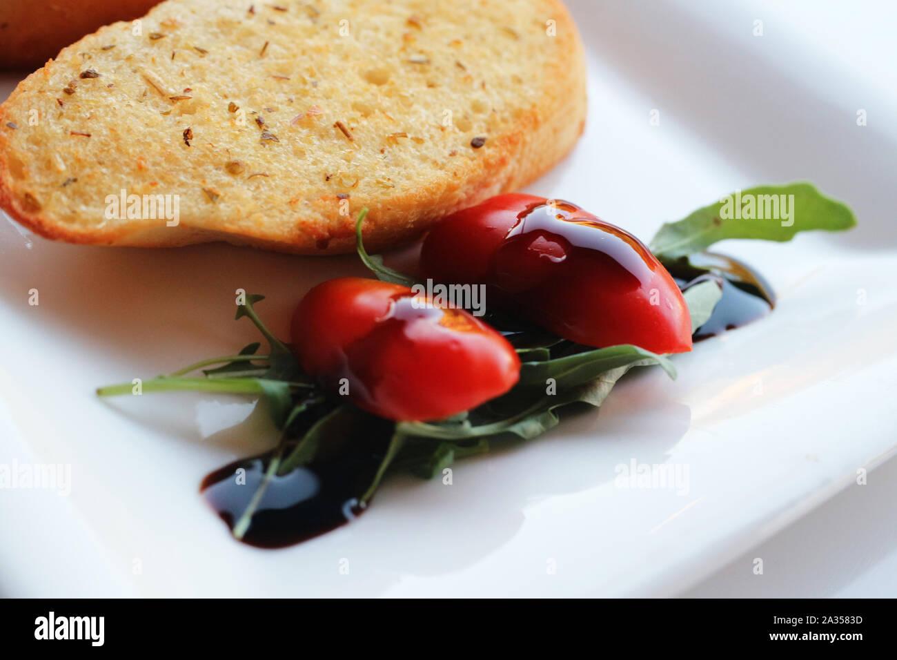 Guarnición de tomate cherry con vinagre balsámico y pan de ajo Foto de stock
