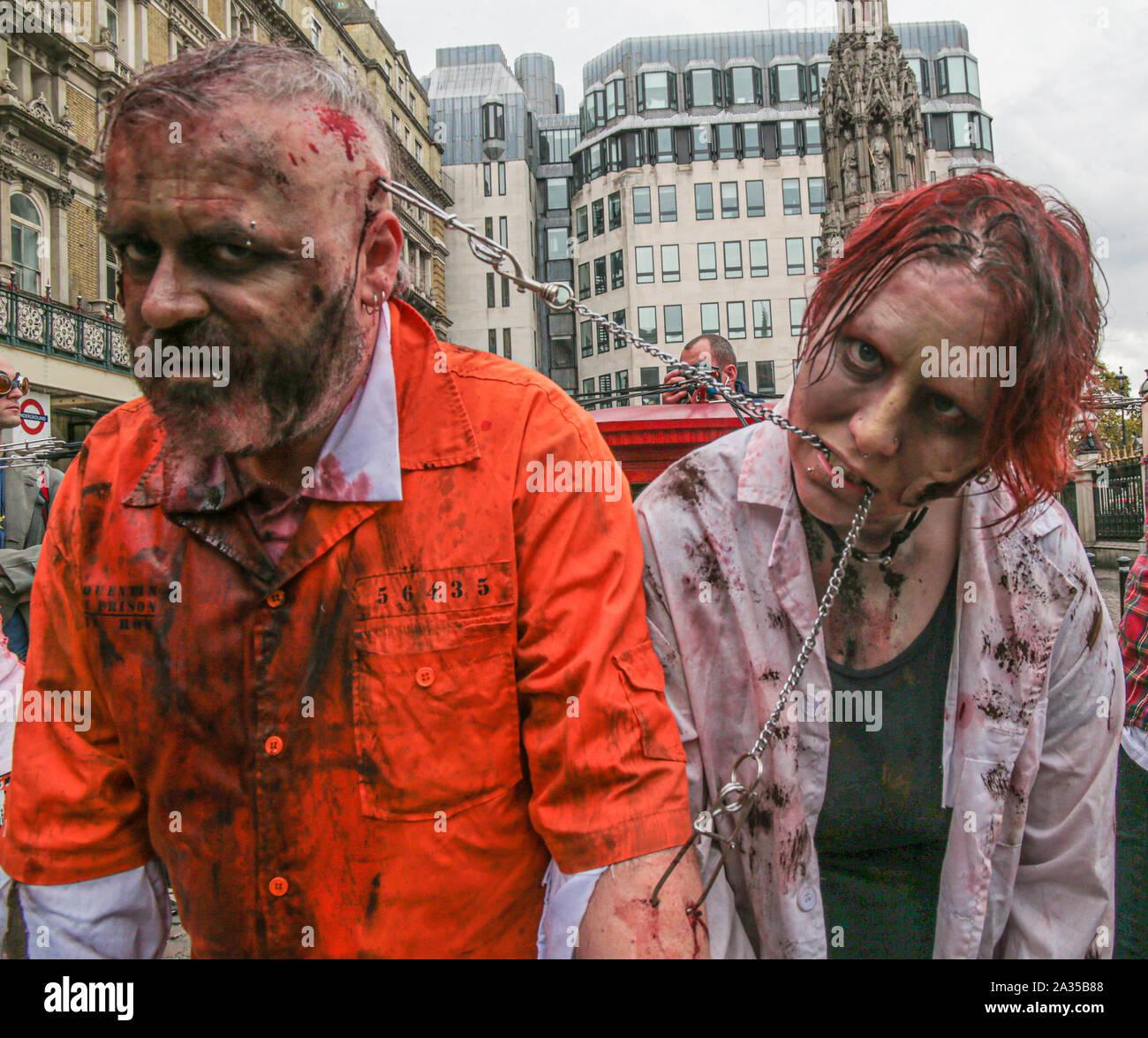 Londres, Reino Unido. El 05 de octubre de 2019. Mientras que la mayoría de los participantes de este año para el día Zombie en Londres ,elegir para vestir y utilizar maquillaje para lucir como scary posible ,este grupo decide ir por el impacto permitiéndose ser tirado por ganchos fijados a sus espaldas por las calles de Londres . Pablo Quezada-Neiman/Alamy Live News Foto de stock