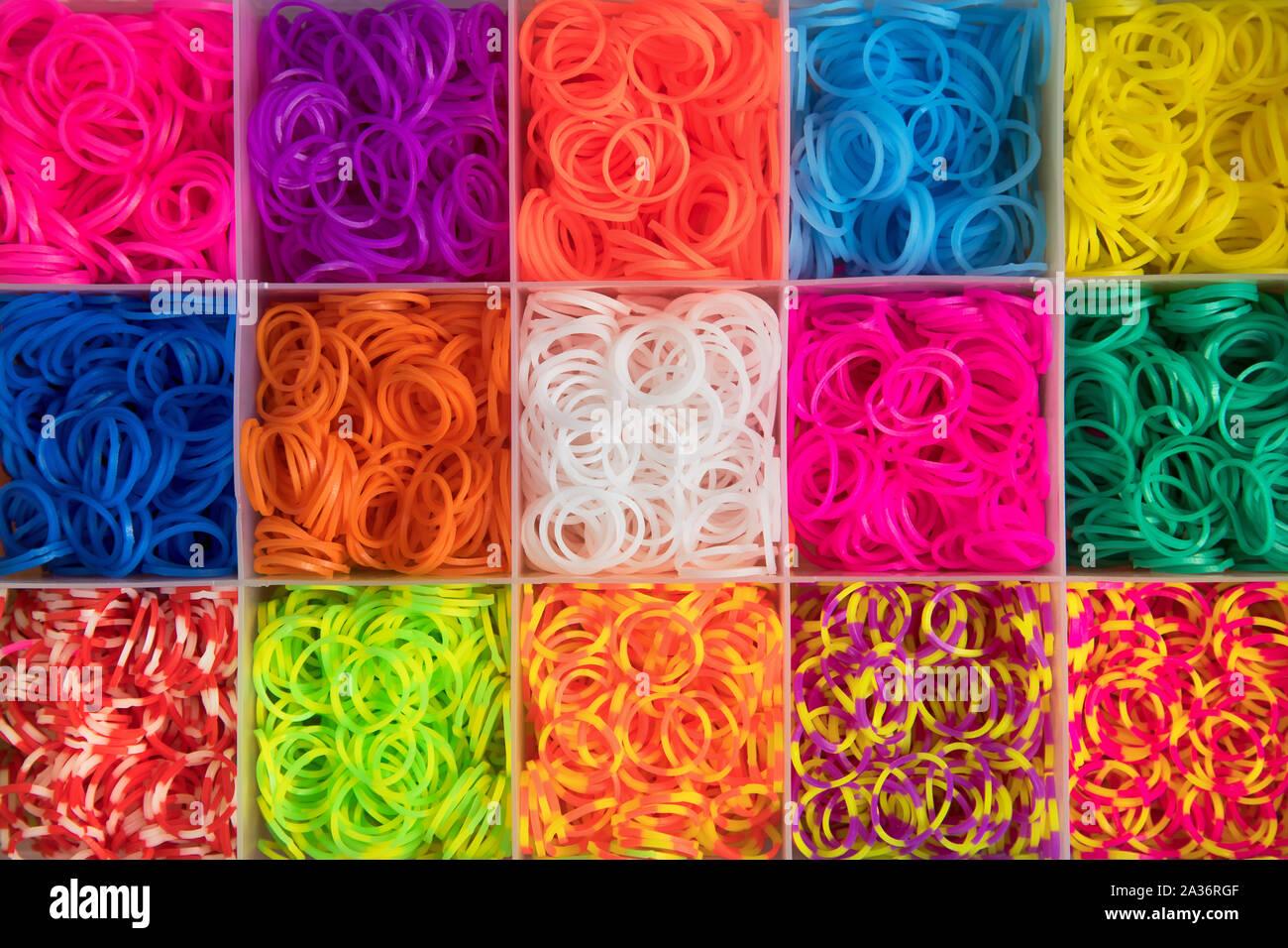 Colorido textura de fondo de bandas elásticas multicolores ordenados en compartimentos cuadrados en una caja vista desde arriba en full frame Foto de stock