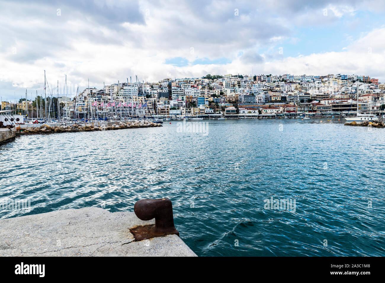 Metal oxidado viejo moorage en el puerto de Atenas, Grecia con la ciudad al fondo Foto de stock