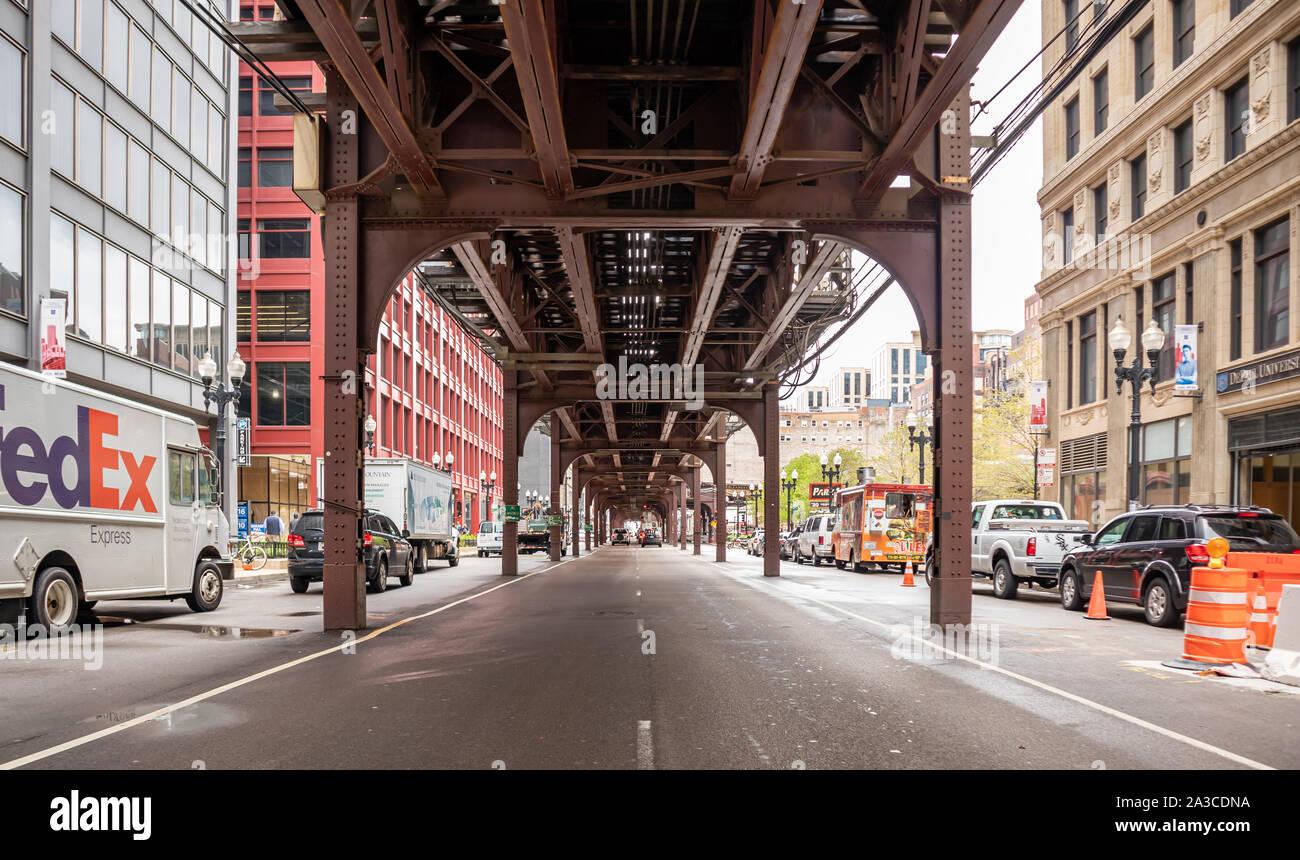 Chicago, Illinois, Estados Unidos, 9 de mayo de 2019. El tráfico en la calle debajo y al lado de un puente de metal con columnas. Transporte en la ciudad de fondo. Foto de stock