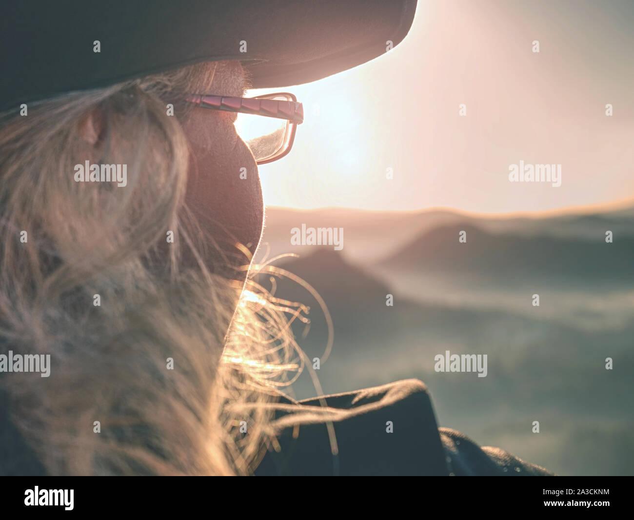 Hermosa joven turista disfrutar el amanecer en la esquina afilada de roca arenisca y tutelarán el valle del sol. Foto de stock