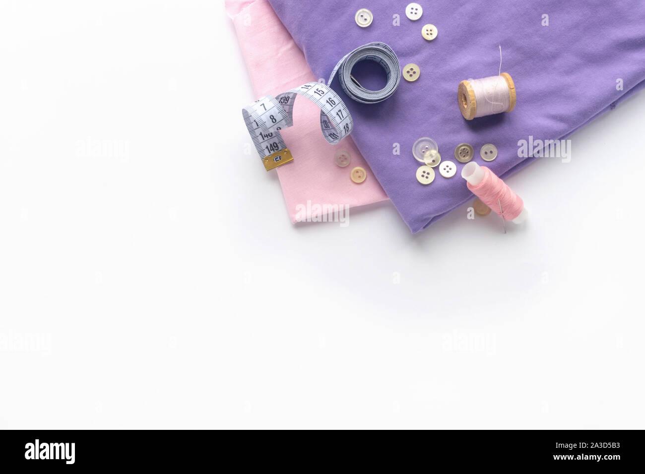 Accesorios de costura y tejido sobre un fondo blanco. Tela, hilos de costura, agujas de coser botones y centímetro. top view, flatlay Foto de stock