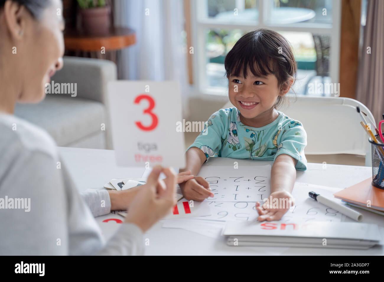 Niño feliz aprendiendo y estudiando, junto con sus padres en casa. homeschooling actividad Foto de stock