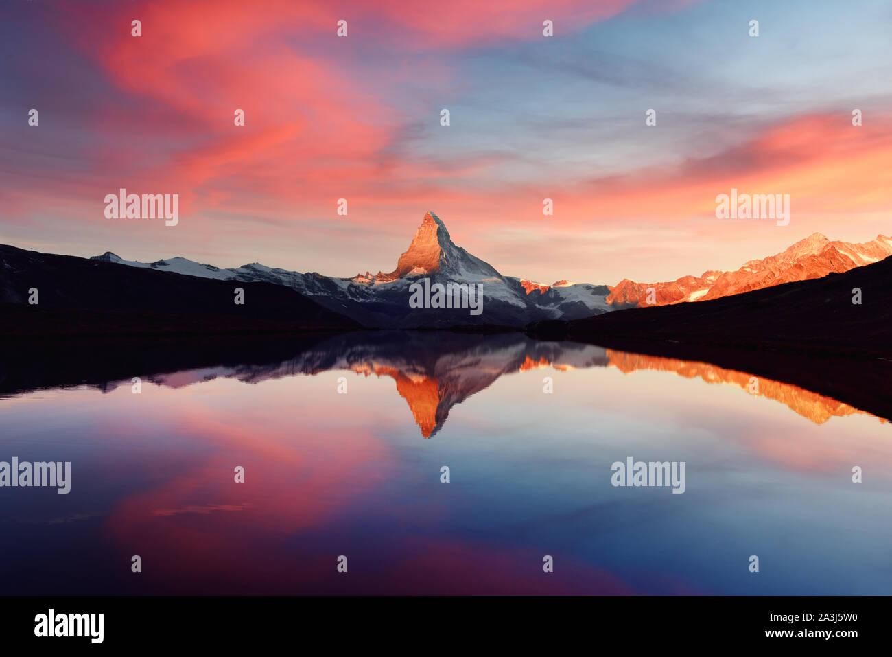 Espléndido paisaje con coloridos Stellisee amanecer en el lago. El Matterhorn Cervino pico nevado con el reflejo en el agua clara. Zermatt, Suiza Alpes Foto de stock