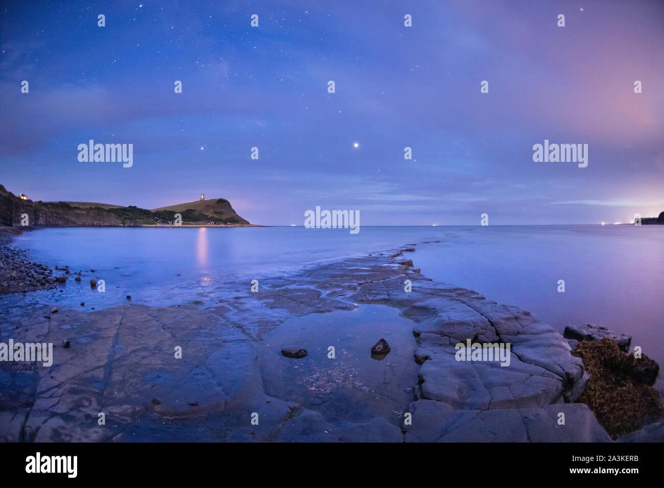 Júpiter y Saturno (centro) (centro izquierda) en el cielo nocturno de Kimmerridge Bay, la Costa Jurásica, en Dorset, Inglaterra, Reino Unido. Foto de stock