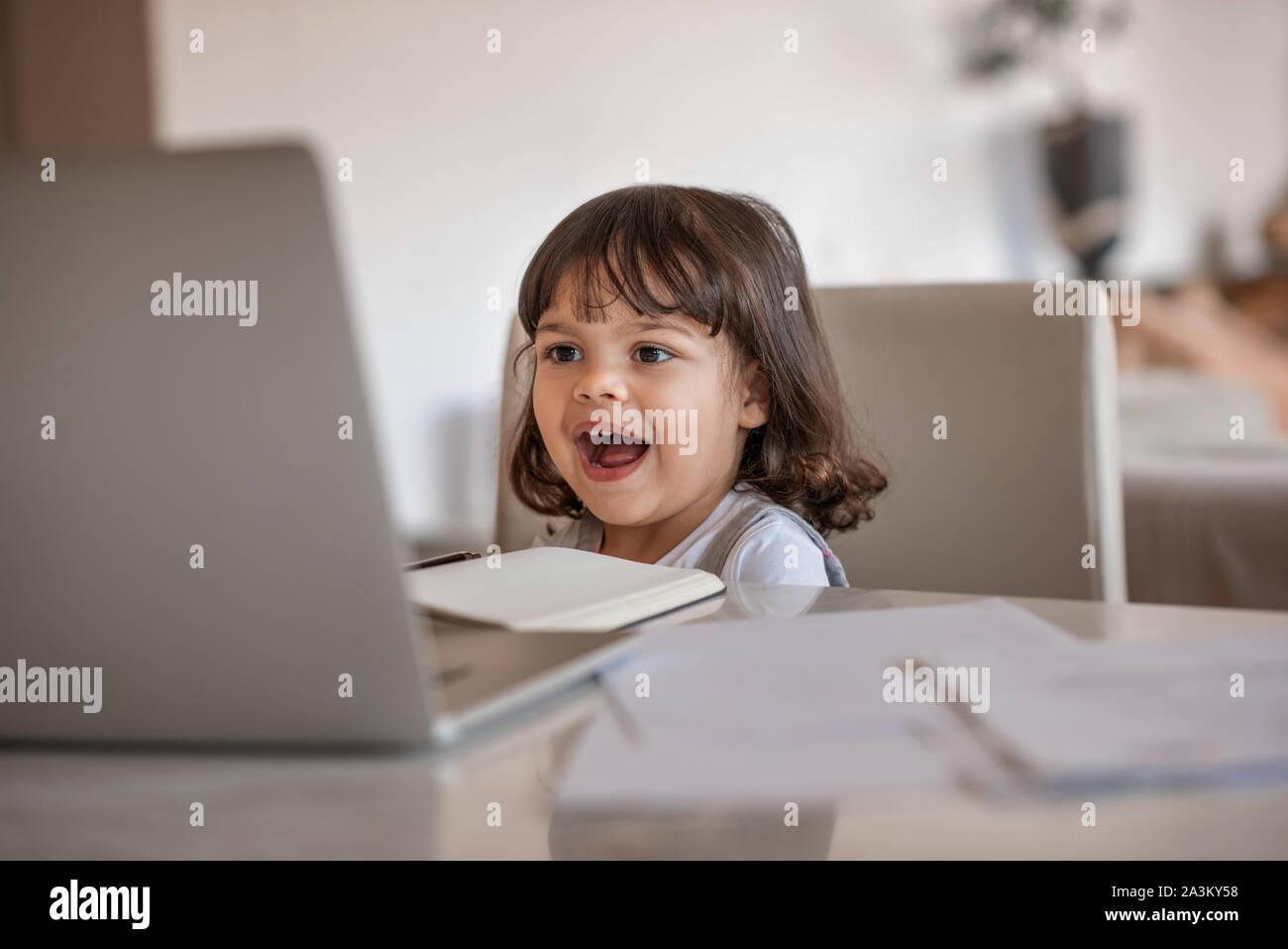 Riendo niña viendo algo sobre su madre laptop Foto de stock