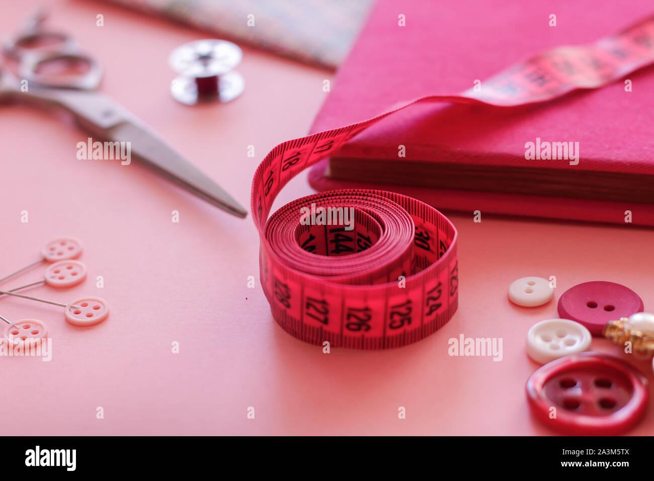 Medir la cinta en color rosa con otros objetos de costura Foto de stock