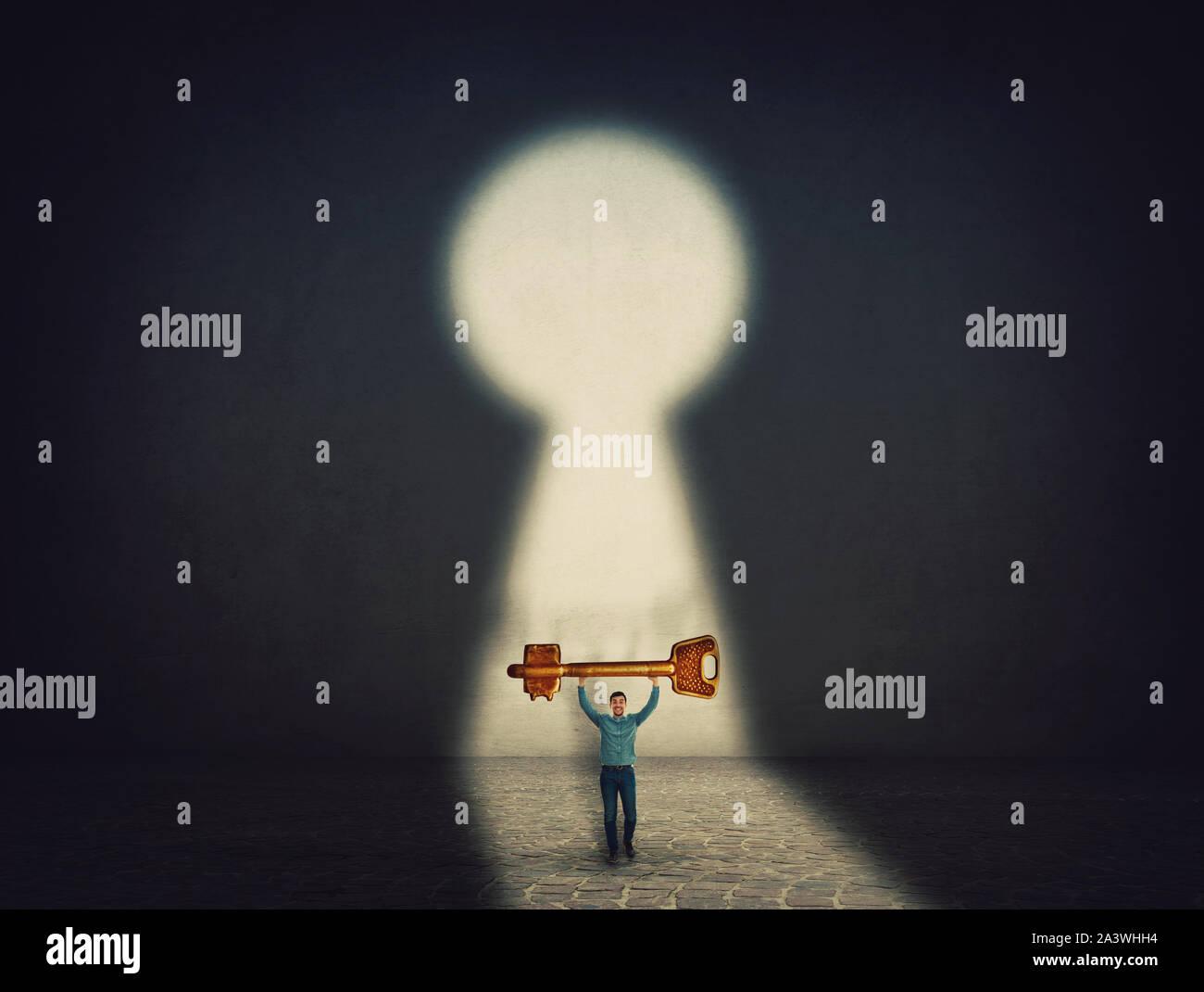 Seguros de empresario lleva una llave de oro por encima de la cabeza, encontraron el camino al éxito, ha de abrir la cerradura. Ambición y motivación empresarial concepto. Desbloquear Foto de stock
