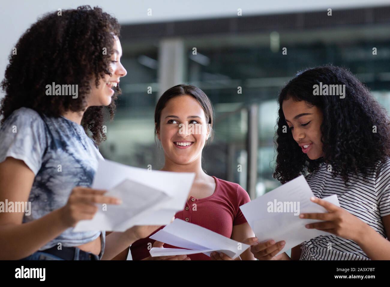 Estudiantes de la escuela secundaria femenina abriendo sus resultados del examen Foto de stock