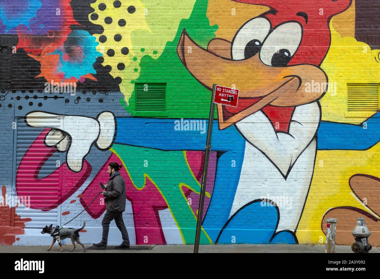El hombre y su perro DELANTE DE UN MURAL efímero, Little Italy, Manhattan, NUEVA YORK, ESTADOS UNIDOS, EE.UU. Foto de stock