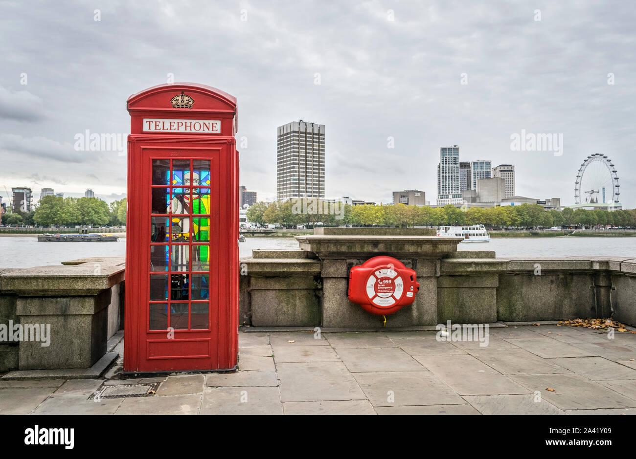 El viejo estilo de Londres Teléfono Caja con vidrieras en el panel posterior con el Ojo de Londres en la distancia y el río Támesis en Londres, Inglaterra Foto de stock